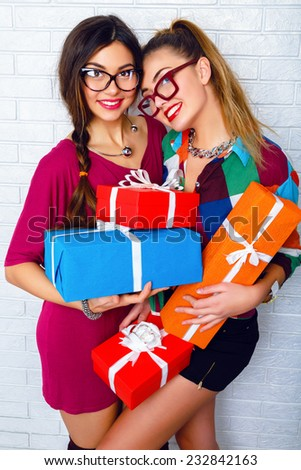 Indoor portrait of two happy best friends sisters girls, ready for holiday party, holding vivd bright gifts and presents, wearing bright clothes and hipster glasses. Urban white background. - stock photo