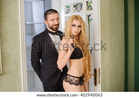 Indoor portrait of young beautiful couple. Relationship concept. Sexy blonde girl with long curly hair is wearing black lace lingerie, lady is pulling the guy by his tie - stock photo