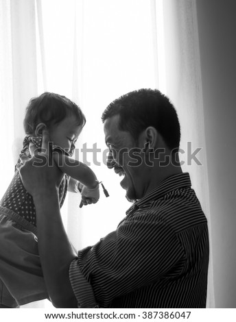 Indoor portrait of young father hugging his little daughter in black and white image. Selective Focus, High Contrast. High Key on the Background - stock photo