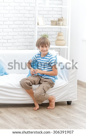 indoor portrait of young happy smiing child boy sitting on sofa at home - stock photo