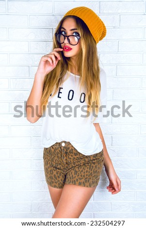 Indoor portrait of young pretty blonde hipster girl with bright sexy lips, wearing swag style printed shorts , glasses and hat. Urban white background. - stock photo