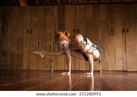Indoor shot of a young yoga instructor doing asanas - stock photo