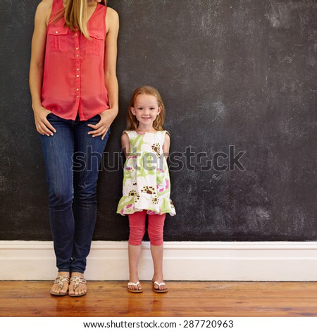 Indoor shot of beautiful little girl standing with her mother smiling. Mother and daughter posing against a black wall with copy space. Woman is cropped in the picture with focus on little girl. - stock photo