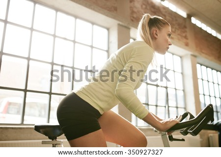 Indoor shot of fit young woman working out on a stationary bike in gym. Determined caucasian female training on exercise equipment in health club. - stock photo