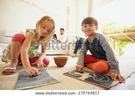 Indoor shot of little children drawing while their father in the background sitting on couch in living room. - stock photo