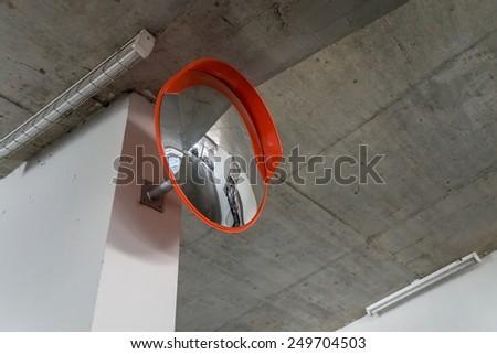 Indoor traffic convex mirror in car parking - stock photo