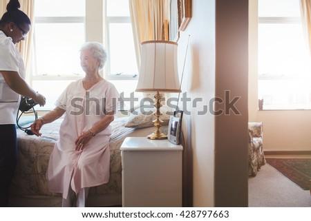 Indoors shot of senior woman's blood pressure being measured by nurse in nursing home. Home caregiver testing blood pressure of old woman. - stock photo