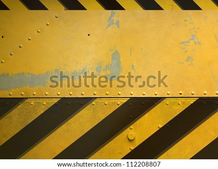 Industrial background, riveted metal plate with caution stripes - stock photo