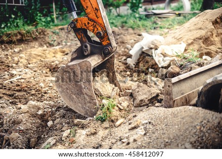 industrial backhoe excavator with close-up of metal bucket moving earth at construction site - stock photo