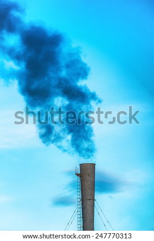 Industrial black toxic smoke from coal power plant on blue sky - stock photo