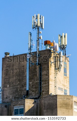 Industrial building with GSM antennas on roof isolated on blue sky. - stock photo