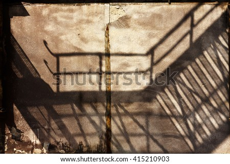 industrial buildings shadows on the wall of an old factory - stock photo