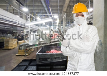 Industrial butcher posing with two filleting knives, wearing protective and hygienic clothing, such as a white suit, mask and a yellow hard hat, in front of a large animal processing plant - stock photo