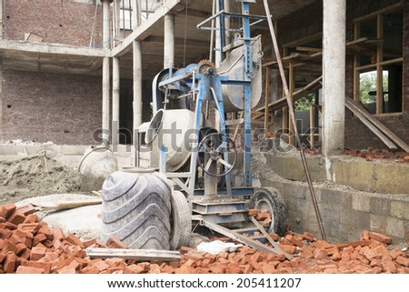 Industrial cement mixer machinery at construction site - stock photo