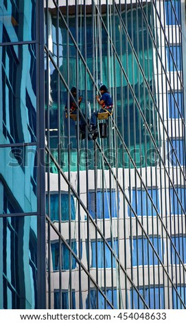 Industrial climber cleaning the glassy wall of Canadian Broadcasting Centre building in Toronto downtown. Front Street West, Toronto, Canada. 2016/06/16 - stock photo