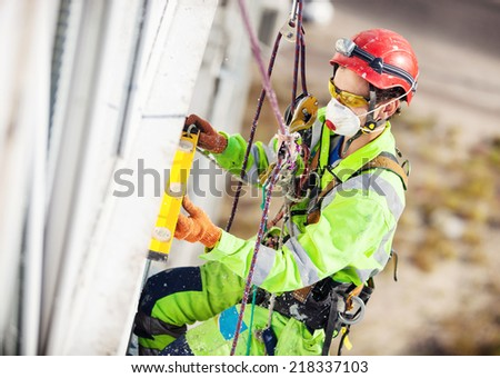 Industrial climber measuring with level tube during construction works - stock photo