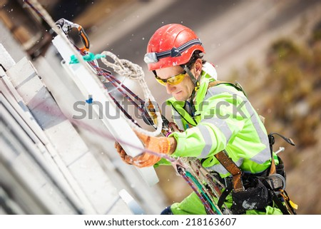 Industrial climber placing a polyfoam sheet insulation to a wall of the building  - stock photo