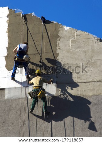 industrial climber workers insulate the walls with Styrofoam plates - stock photo