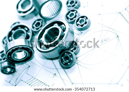 Industrial concept. Few ball bearings on graph paper background with blueprint - stock photo