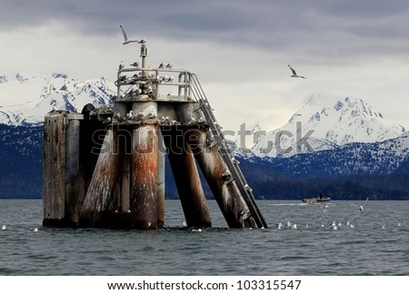 Industrial concrete pier pillar in the Kachemak Bay in Alaska with gulls and a boat and the Kenai Mountains in the background on a stormy day. - stock photo