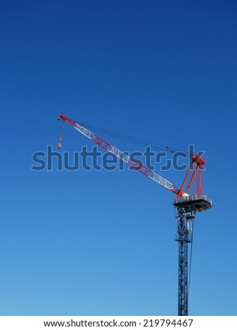 Industrial construction crane in the blue sky background - stock photo