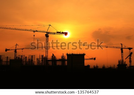 Industrial construction cranes and building silhouettes - stock photo