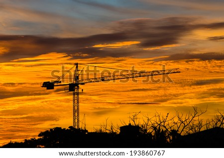 Industrial construction cranes silhouettes at sunrise. - stock photo