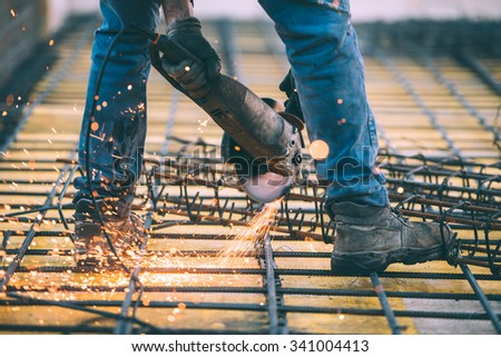 Industrial construction engineer cutting steel using angle mitre saw, grinder and tools. Filtered image with retro effect - stock photo