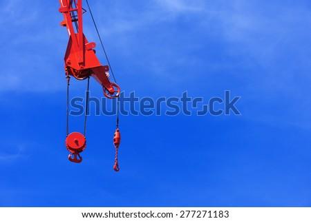 industrial crane hook against blue sky - stock photo