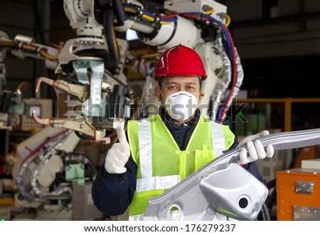 Industrial engineer holding metal production with giving thumb up - stock photo