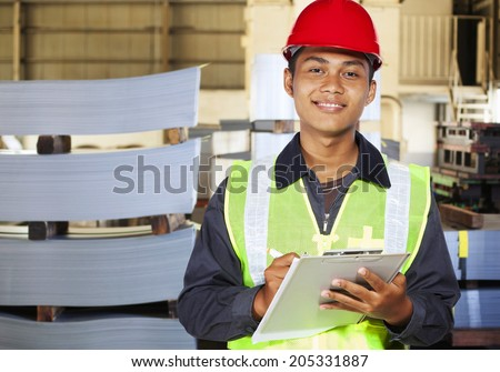 Industrial engineer holding notepad in factory - stock photo