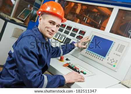 industrial engineer worker operating control panel system at modern manufacture plant - stock photo