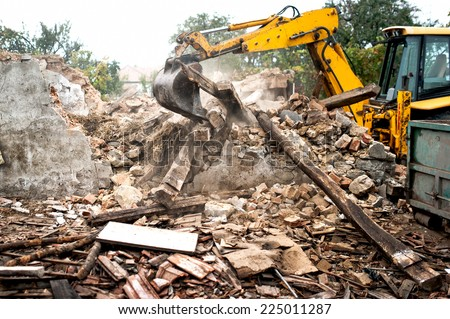 industrial excavator and bulldozer loading debris and demolition concrete walls into a container - stock photo