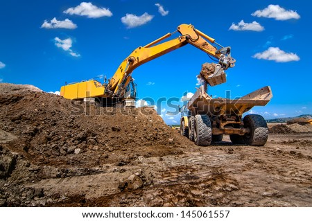 industrial excavator loading soil from sandpit into a dumper truck - stock photo