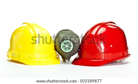 Industrial hardhats and respirator on white background; protective devices for workers - stock photo