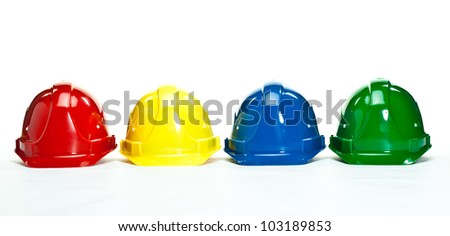 Industrial hardhats on white background; four multicolored construction hardhats - stock photo