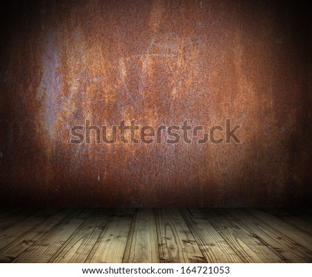 industrial interior background with rusty metal wall and wood floor - stock photo