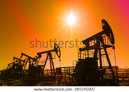industrial landscape oil pumps in the early spring on a sky background instagram filter - stock photo