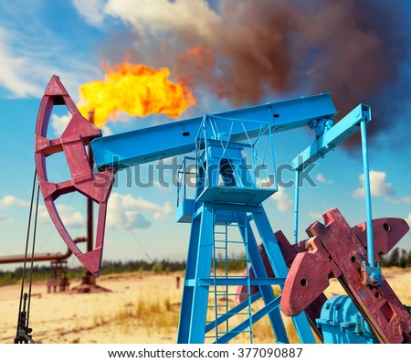 Industrial landscape. Oil rocking chair on the torch and the cloudy sky background. - stock photo