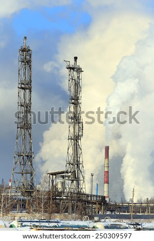 industrial landscape smoke from the chimneys large plant and power lines against the blue sky in winter - stock photo