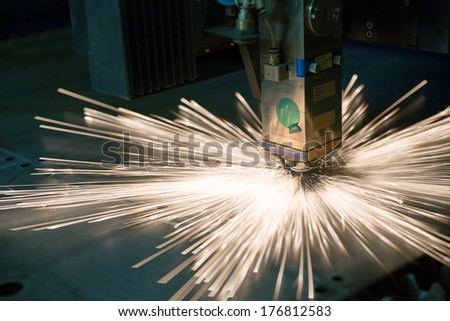 Industrial laser making holes in metal sheet - stock photo