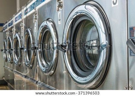 industrial laundry machines in laundrette - stock photo