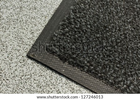 Industrial mats often rented to keep dust levels down in commercial business buildings, warehouses or anywhere with polished, plastic or sealed floors - stock photo