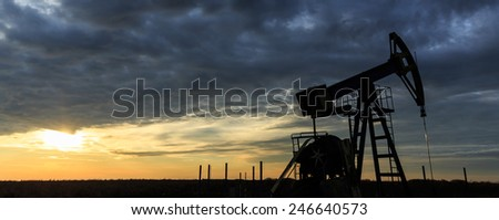Industrial oil and gas well pump at sunset - stock photo