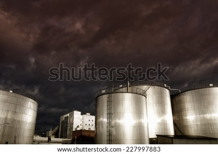 industrial oil storage tanks at sunset, sun gleaming in metal - stock photo