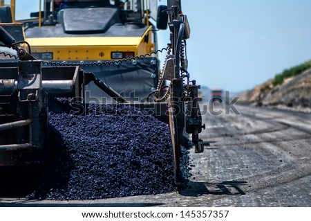 Industrial pavement machine laying fresh asphalt on highway construction site - stock photo