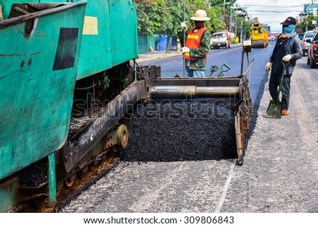 industrial pavement truck laying fresh asphalt on construction site - stock photo