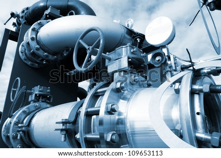 industrial pipelines and valve in blue tones - stock photo