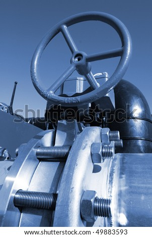 industrial pipelines on pipe-bridge against blue sky - stock photo
