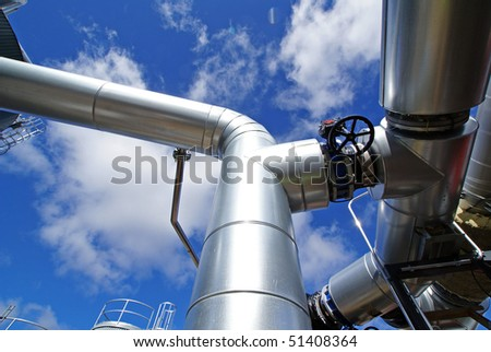industrial piping and valves against blue sky - stock photo